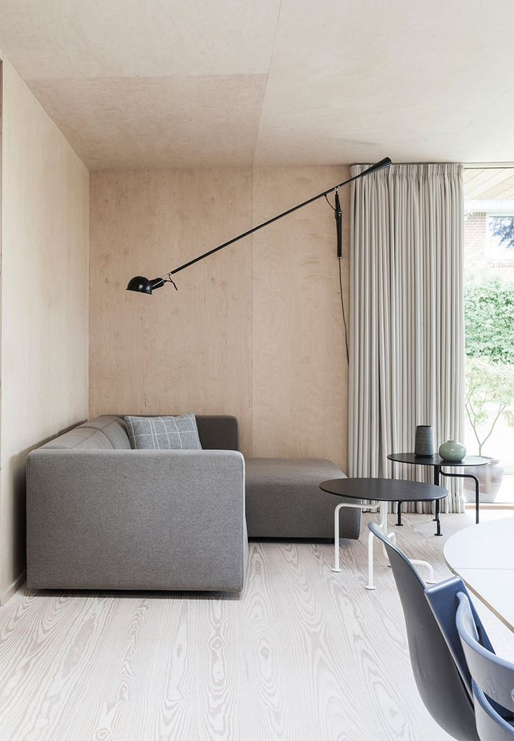 The living room is in birch veneers, which, with its decorative structure, makes art on the walls almost superfluous. The black elements give some edge to the bright wooden walls and the gray Match L sofa from Prostoria and the sofa pillow from Oyoy.