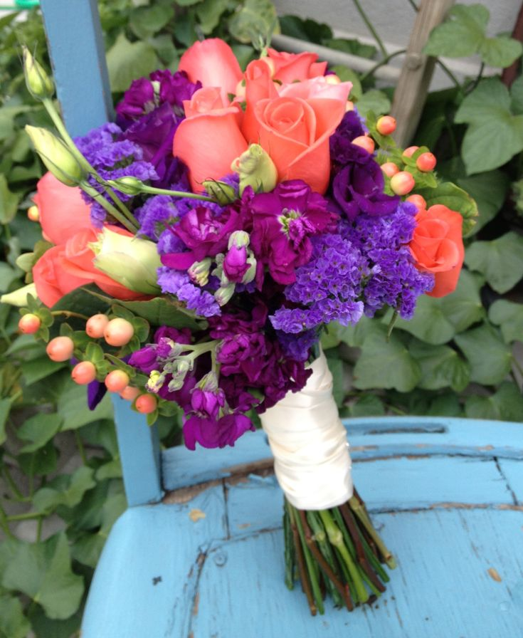 Great coral and purple bouquet using coral roses, purple stock, status, purple lsianthus and hypericum berries