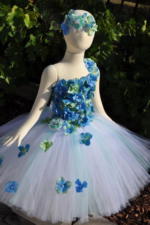 Deze verbazingwekkende bloemenmeisje / speciale gelegenheid Tutu jurk is gemaakt met wit tule met accenten van beide bleke oceaan blauw of zee schuim groene tulle en komt op een wit Gehaakt topje. Het lijfje is versierd met trapsgewijze Hydrangea bloemen van blauw en zee schuim groen met genaaide parel centra. Een afneembare Shabby Chic bloem kan overal gedragen worden op de jurk of heeft een accent stuk. Weergegeven, is de enkele satijn schouderband maar u kan ook kiezen een halster of ...