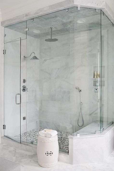 an angled seamless glass shower is clad in large gray marble staggered tiles on ceiling and wall accented with three shower heads alongside a gray mosaic