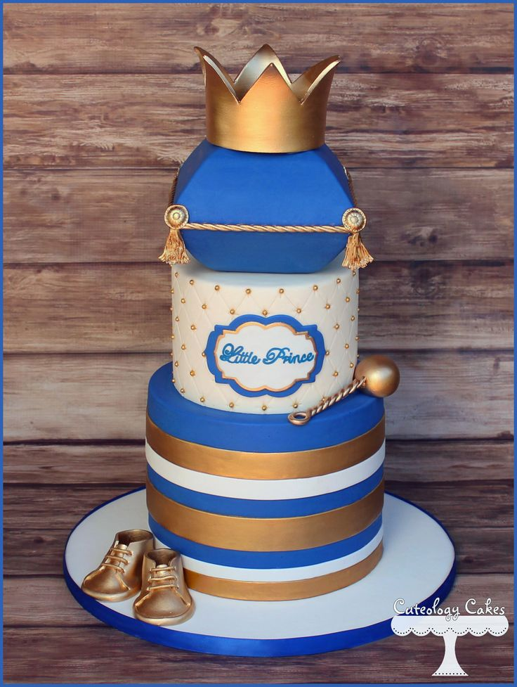 Prince themed baby shower cake in royal blue and gold with crown, baby shoes, and rattle. www.facebook.com/i.love.cuteology.cakes