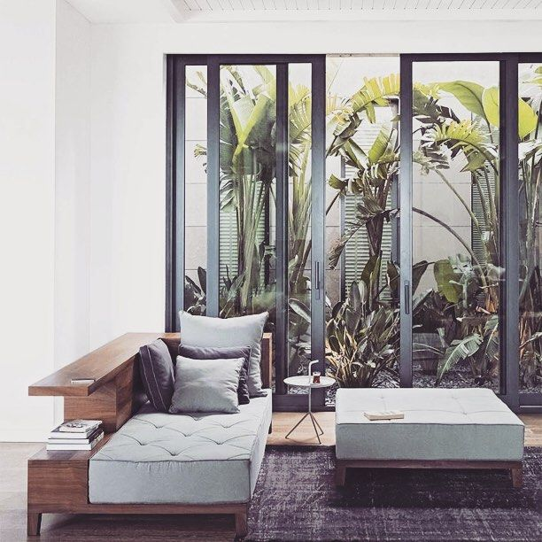 Mid century conservatory. Make the most of a small courtyard space with large sliding doors that can be pulled open in the warmer months.  #theROOMedit #home #style #decor #interior #interiordesign #inspiration #midcentury #conservatory #lounge #rug #jungle #oasis #green #outdoor #minimalist by theroomedit