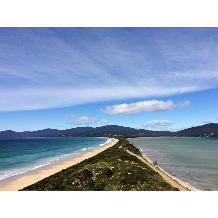 """""""Back to Back"""" perfectly describes the isthmus on Bruny Island that is the sweep of ocean on one side and the sheltered waters of the D'Entrecasteaux Channel on the other. Barely wide enough to contain the road that links the north and south of Bruny, This is a much photographed and explored piece of Tasmania.  Image credit: T Loh"""