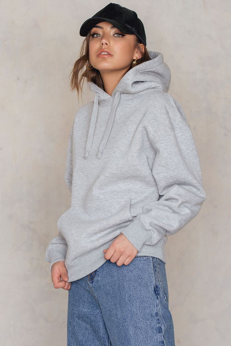 Girl! Whether you like it or not, the hoodie trend is back! The Hoodie Sweater by Vanessa Moe for NA-KD comes in the color grey melange and features a drawstring hood, ribbed cuffs, and hem with a pouch pocket, a black printed Arabic text at the back that says Vanessa Moe, fleece lined and the sweater comes in a soft-touch sweat material with an oversized fit. This sweater is a must-have for cozy days to lounge around in! Style with trainers and denim jeans!