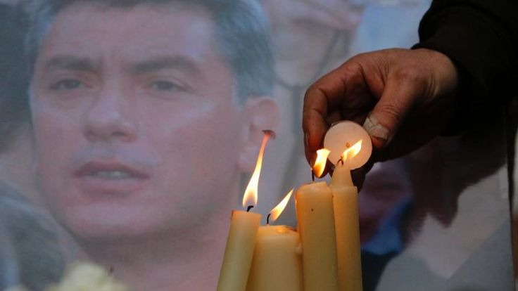 People light candles in memory of Boris Nemtsov, seen behind, at the monument of political prisoners 'Solovetsky Stone' in central St.Petersburg, Russia, Saturday, Feb. 28, 2015. Nemtsov was gunned down Saturday near the Kremlin, just a day before a planned protest against the government. (AP Photo/Dmitry Lovetsky) (The Associated Press)