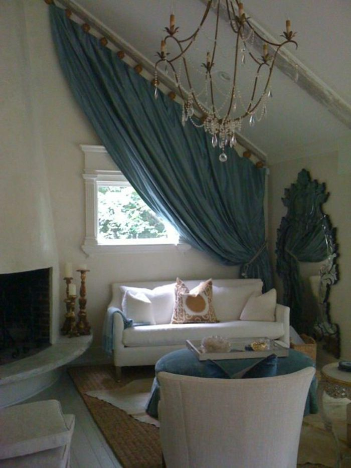curtains for living room, small white sofa and chair, mirror and TV, small window with plaster details, half-covered by long teal curtain