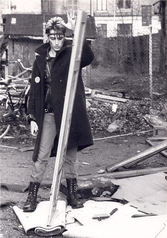 Det her billede er taget i 82/83 på Nørrebro, lige der hvor Stengade møder Baggesensgade. Michael Valeur, som er på billedet, var digter. Han skulle udgive sit første kassettebånd på Irmgardz og syntes, at jeg tog gode billeder. Dengang blev Nørrebro renoveret, så der lå meget byggeaffald over det hele. Du kan se han står med en lokumsdør eller sådan noget. Han skrev meget om punk i sine digte, som han optrådte med i et show, hvor ham og en anden samplede lyde, hvilket var umuligt dengang…