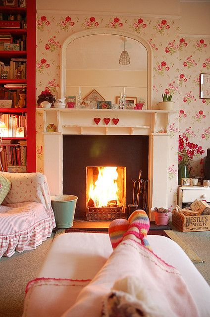 Charming fireplace, wallpaper & furnishings make this a delightfully cozy, comfortable room. I love the dark pink (almost red) floor-to-ceiling bookshelves and the way they coordinate so well with the wallpaper.