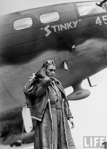 "8Th Air Force Bomber Command An Amer. airman clad in heavy sheepskin jacket & pants holding up one heavy insulated boot as he poses proudly next to the nose of his B-17 Flying Fortress bomber decorated the name ""STINKY"" 45, parked at US 8th Bomber Command airdrome. Sept. 1942."