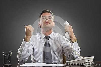 Happy successful businessman celebrating with raised clenched fists his business success news received on the telephone in his office against grey background.