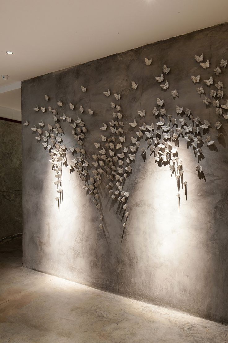 concrete-effect feature wall with butterflies by Vivarium / HYPOTHESIS + Stu/D/O Architects