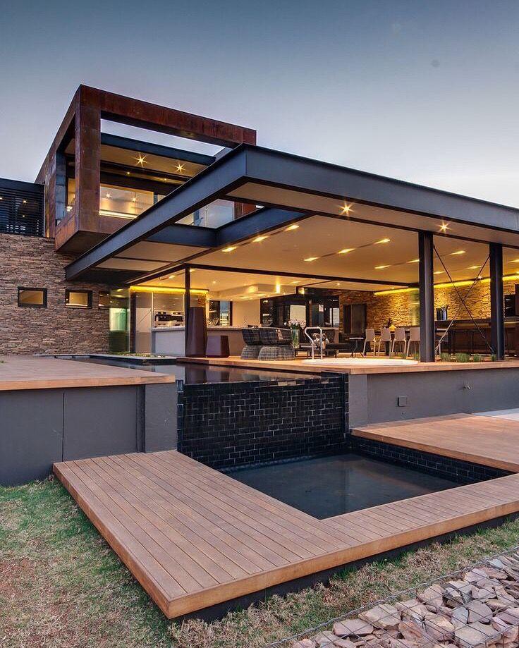 Casa moderna utilizando de mateira e detalhes em concreto para integrar à natureza, ambientes envidraçados e iluminação confortável.