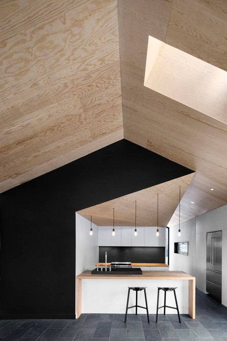 plywood ceiling / cathedral ceiling / black accent wall / contemporary kitchen / skylight / black + wood + white