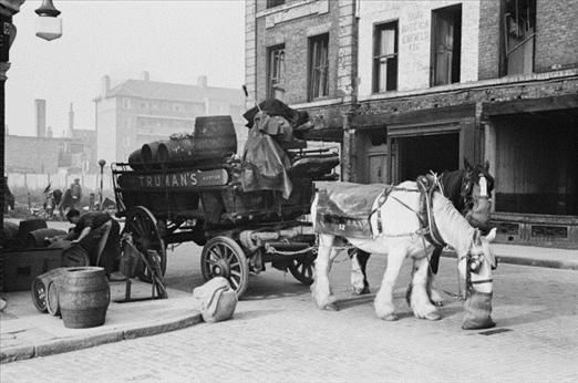 Men unloading barrels of beer outside a pub in the Pool of London, while their carthorse feeds from a nosebag, December 1949. Original publication: Picture Post - 4931 - The Pool Of London - pub. 3rd December 1949. Photo by Bert Hardy (19 May 1913 - 3 July 1995) / Picture Post / Hulton Archive/Getty Images)