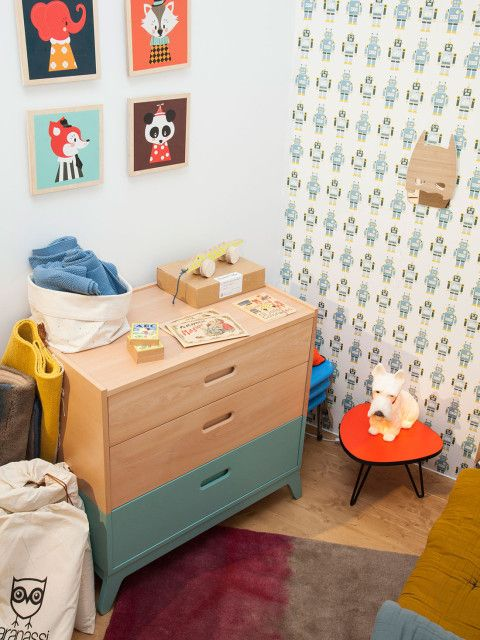 Two tone wood and painted mid century modern dresser and robot wall paper give this nursery retro pop.