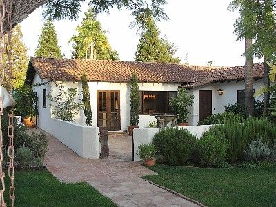 Spanish Revival Bungalow with low walls and angled entry front courtyard.