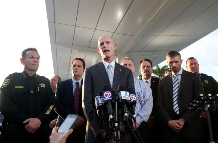 Joined by law enforcement officials, Florida Gov. Rick Scott, center, speaks during a news conference outside Fort Lauderdale–Hollywood International Airport, Friday, Jan. 6, 2017, in Fort Lauderdale, Fla. A gunman opened fire in the baggage claim area at the airport Friday, killing several people and wounding others before being taken into custody in an attack that sent panicked passengers running out of the terminal and onto the tarmac, authorities said.
