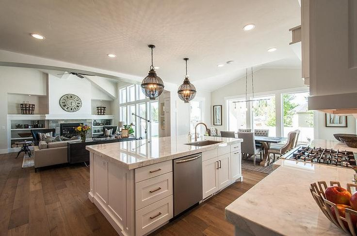 Amazing kitchen features a pair of black cage lanterns placed above a white center island topped with white quartzite countertops fitted with an off set ...