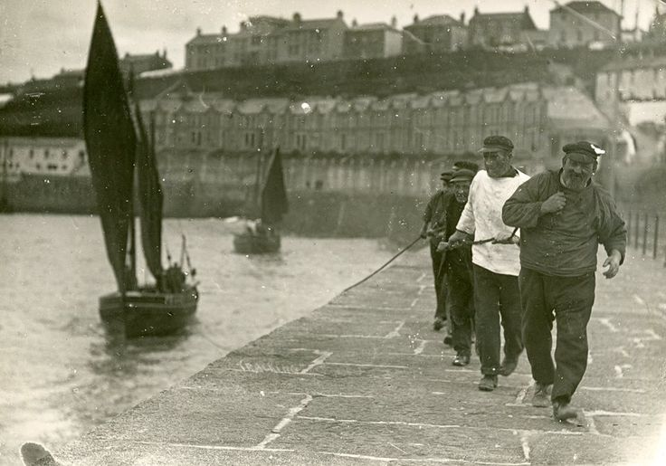 FIVE FISHERMEN TRACKING A BOAT (c.1930s-50s) | Porthleven, Cornwall: 'Tracking is the practice of pulling a boat out of the harbour to catch the wind at the end of the pier. The fishermen are on the pier pulling one boat and another boat is following. Bay View Terrace and the Coastguard Cottages in Peverell Road are in the background.' (pic. A H Hawke of Helston | text Helston Museum)     ✫ღ⊰n