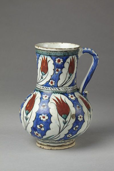 Jug | Made in Iznik, Turkey, ca. 1600 | Materials: fritware, polychrome underglaze painted, glazed | Jug of fritware, painted with two rows of leaf-shaped compartments on a blue ground, each enclosing a tulip in red and green | VA Museum, London