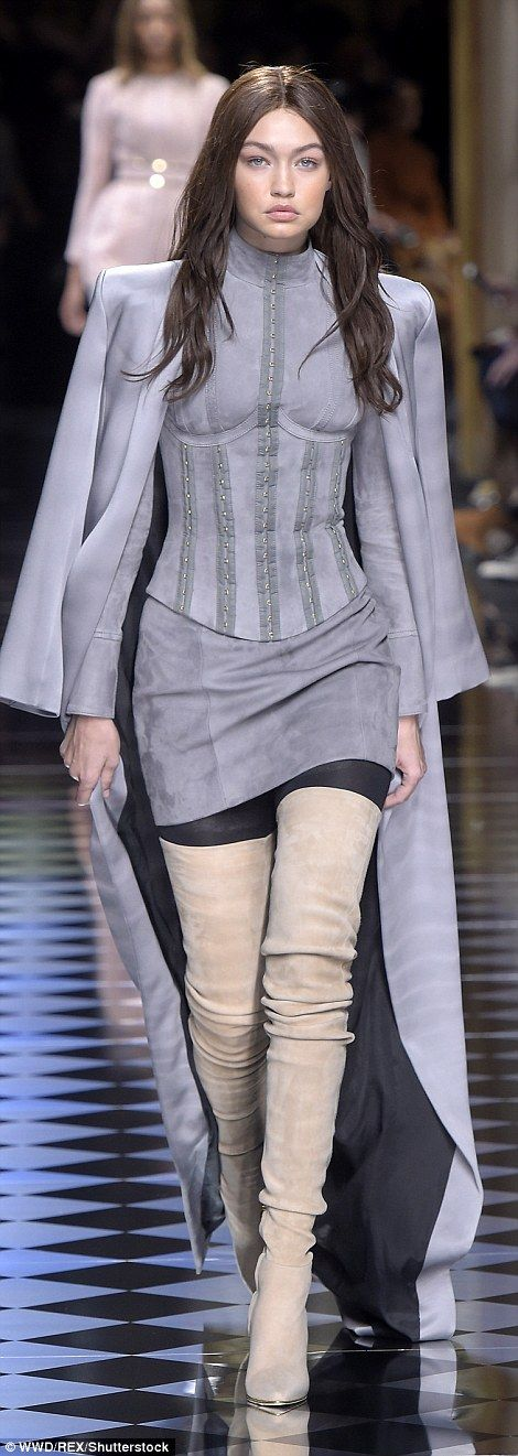 Complementary look: Gigi covered up in a matching corset top which was high-necked as well as a sexy mini and thigh-high boots