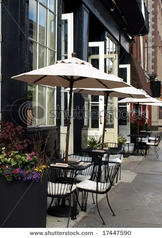 Doors Open Out From The Indoor Restaurant To An Outdoor Cafe With Tables  Under Umbrellas.