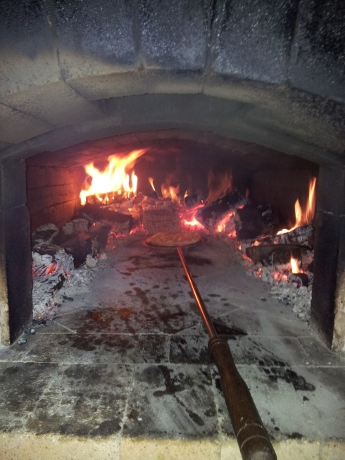 Pizza cooking in the wood fired oven