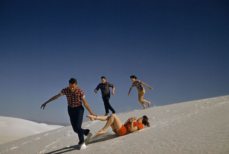 Teenagers run and play on large white sand dunes in New Mexico, 1957. Photograph by J. Baylor Roberts, National Geographic