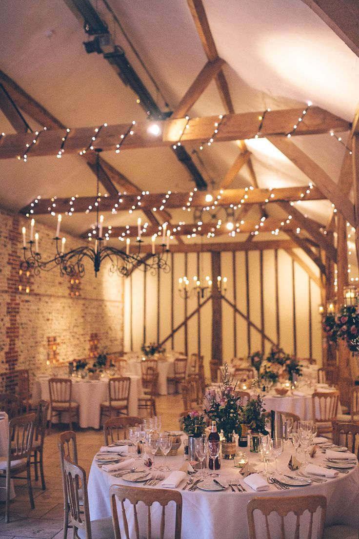 Rustic barn with fairy lights wrapped around the beams - Image by Story & Colour - Bride in Tea Length Lace Justin Alexander Dress with birdcage veil & Rachel Simpson Shoes. Bridesmaid in Hobbs navy dress for a rustic barn wedding with berry blooms, naked cake & nautical theme.