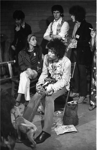Jimi Hendrix, Monterey, CA, 1967 Backstage ( which was under the stage ) at the Monterey Pop Festival. This was either just before or just after Jimi performed. Probably after because he was eating fried chicken. Behind him are John Entwistle, bass player for the Who and Noel Redding, bass player for the Jimi Hendrix Experience.