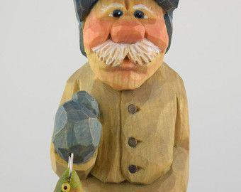 Lars ist ein begeisterter Fischer, Sommer und Winter. Auch in der Tiefkühltruhe der nordischen Winter in seinem Eishaus oder der Regen und raue Gewässer auf den Fjorden im Sommer, Lars trägt ein Lächeln und ein Funkeln in seinen Augen hat. Er steht 5,5 Zoll (14 cm) groß und wurde liebevoll von nördlichen Lindenholz geschnitzt. Seine Regenbogenforellen misst 1,5 Zoll (ca. 4 cm) lang und ist auch aus Lindenholz geschnitzt. Was für ein Fang