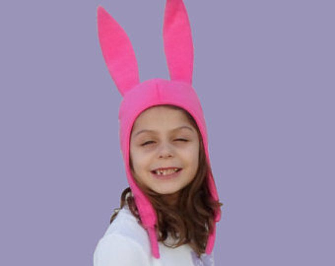 Louise Belcher Hat Pink Bunny Ears Hat   These hats are professionally handcrafted from Anti pill fleece that stretches out making the hat easier to fit.   The ears are framed with wire that allows to stand up and shape as desired. The hat has ear flaps, short ties and its fully lined with cotton knit.   19 to 20 Head circumference -------------- size S 20 to 21 Head circumference -------------- size M 21 to 22 Head circumference --------------- size L 22  to 23 Head circumference…