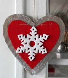 Grote houten hanger beplakt met rood vilt en daarop een wit, keramiek sneeuwkristal ornament. De hanger lijkt een beetje Skandinavisch.    Handgemaakte, unieke hanger. Bijbestellen kan, maar deze wordt nooit excact hetzelfde.    Afmetingen: 18, x 18 x 1 cm. (1,5 cm. inclusief ornament.) Het ornament is 10 x 10 cm. van punt naat punt. / Brievenbuspost.
