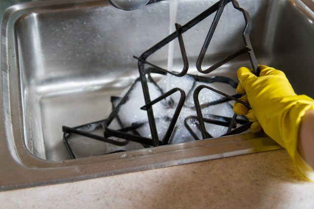 Stuck-on food, grease and oil spills on a gas stove's cast-iron grates create nasty fumes and smells. These strong, heavy grates benefit from a once-a-month, if not more, cleaning to keep your kitchen odor free while you cook. The methods used to clean them depend on how dirty they are.