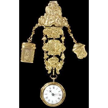 In the middle is a watch, which bears the name of the watchmaker, Robert Cawley, Chester, movement no. 91. The watch and the small empty container or étui on the right are of approximately the same date as the chatelaine.In the middle is a watch, which bears the name of the watchmaker, Robert Cawley, Chester, movement no. 91. The watch and the small empty con...