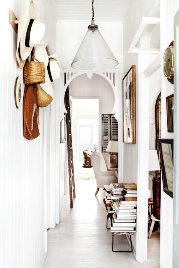 I like the architectural detail in the doorway. nice way to break up all the sharp rectangular lines in a hallway. White on white with a nice touch of 'natural' from hats, picture frames and other hanging things.