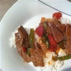 Round steak strips are sauteed with green pepper and simmered with diced tomatoes, garlic, and ginger in this easy meal. Serve over steamed rice.