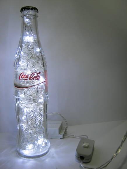 Luminária produzida com garrafa de vidro da marca Coca-Cola Zero, refrigerante comercializado em mais de 200 países.   Além de original, é duplamente sustentável: a garrafa é um material reciclado e o LED consome menos energia e tem vida útil bem mais longa do que as lâmpadas comuns.  Ideal para cabeceiras, estantes e escrivaninhas. Combina também com ambientes comerciais como lojas, bares e restaurantes.  Características:  - São 50 microlâmpadas brancas de LED que permitem uma boa…