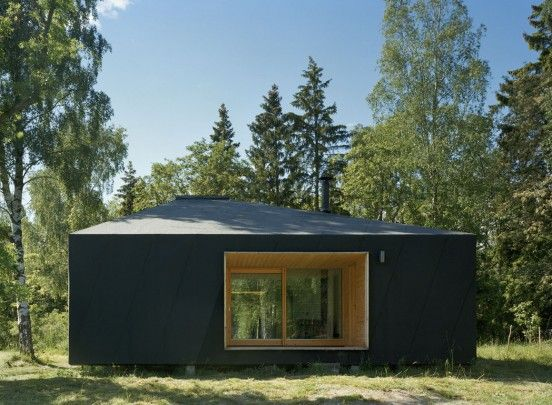 Söderöra – Summer House in the Stockholm archipelago. The roof and facades are wrapped in black roofing felt, whilst patio spaces and interior surfaces are made of sawn wood panelling.