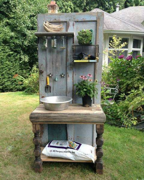 Potting bench made from am old door and wood scraps, bowl and old table.