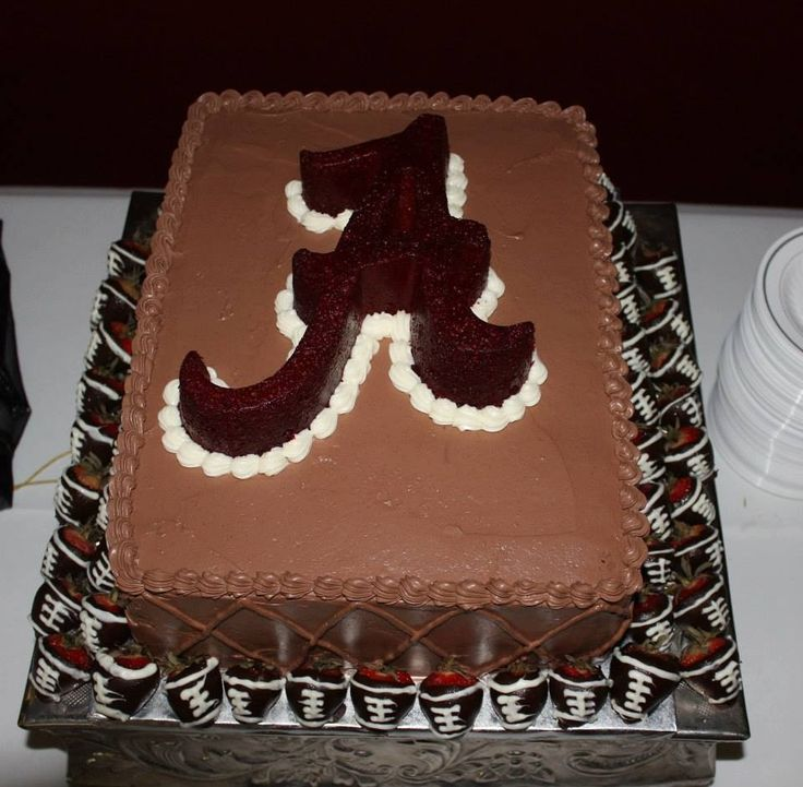 """Alabama Grooms cake  - Chocolate cake with whipped icing, red velvet """"A"""" unfrosted with a cream cheese border.   Football dipped strawberries around the base."""