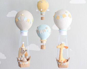 Bebé elefante y globo de aire caliente móvil en aqua, gris y blanco. Un adorable elefante flotando a lo largo con un globo de aire caliente en 3D impreso barco. Este bebé móvil es simplemente adorable en aqua y en gris para una fantástica adición a un vivero de tema de viaje.  Todo creado a mano en mi estudio de la tela. Rellena con relleno de poli y adornado con varios botones, lazos, pompones y cinta. Acabado con canastitas impresos de 3D para una mirada de mimbre true. Los globos se…