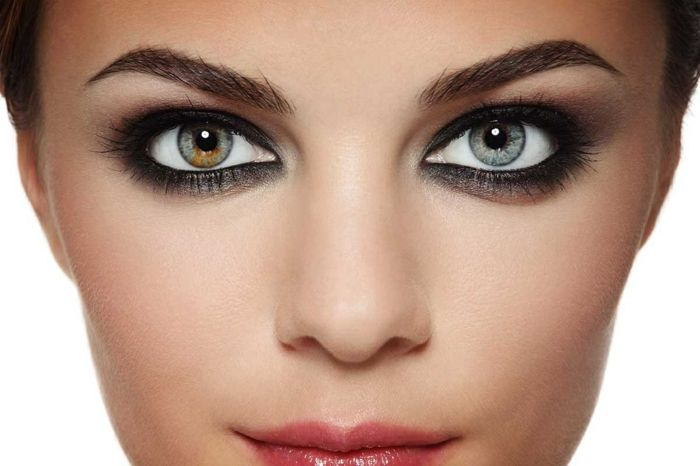 different colored eyes, extreme close up of woman with one light blue and one multicolored eye, black eye-make up and pink shiny lipstick