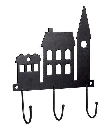 Zwart. Een metalen wandrekje met drie haken. Het rekje is versierd met de silhouetten van gebouwen en heeft twee schroefgaatjes voor montage aan de wand.