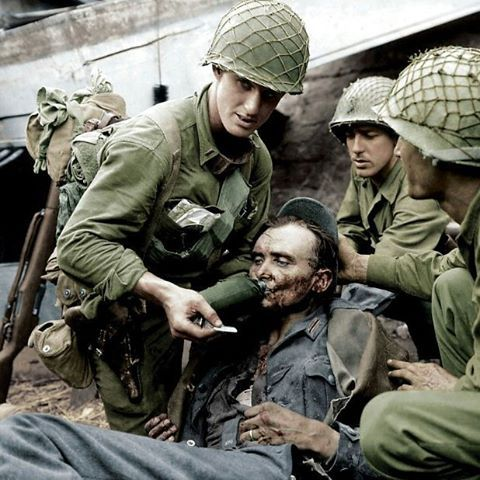 American soldiers helping a wounded German POW looks like one of the Americans got himself a luger