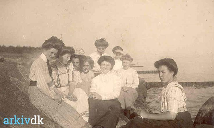 arkiv.dk | Gruppebillede af unge piger på udflugt en sommerdag ved vandet. Yderst til højre i billedet sidder Ingeborg Hoff Holm, der blev født d. 06.10.1895, hun var en af de første telefonistinder i byen.