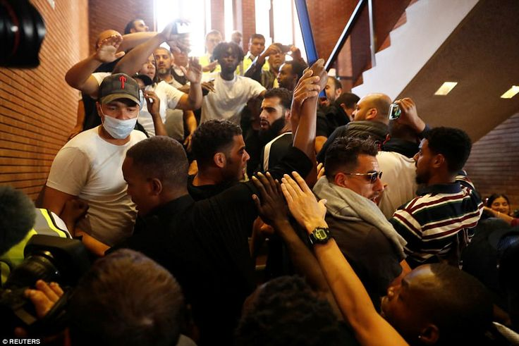 Demonstrators crowd onto a staircase as they storm Kensington Town Hall in London today...