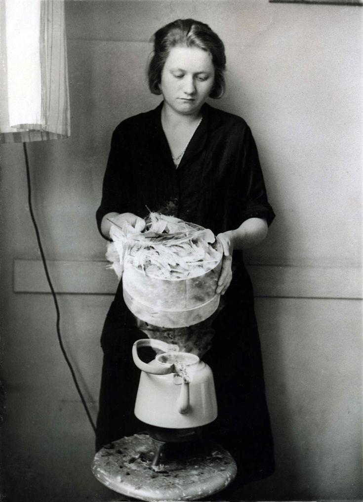 Garnituren: vrouw bezig met de fabricage van mode accesoires van ganzenveren: stomen boven een ketel. Duitsland, 1932.