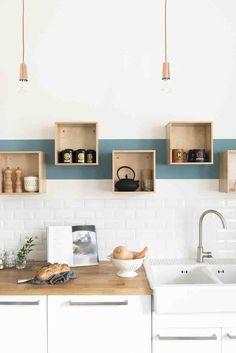 Bande bleu sur mur blanc, lampes bronze, étagères-caisses et plan de travail en bois.