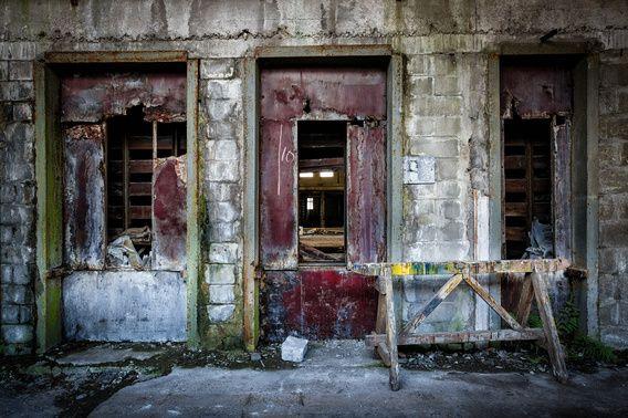 De drie rode deuren in een verlaten fabriek van Steven Dijkshoorn